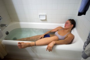 """UFC women's bantamweight champion Ronda Rousey soaks in a hot bath under the supervision of MMA nutritionist Mike Dolce during her last night of weight cut after a workout inside her hotel room Thursday February 26, 2015. Rousey will be defending her title against No. 1 contender Cat Zingano in the main event of UFC 184: ROUSEY vs. ZINGANO on Saturday, Feb. 28 at Staples Center in Los Angeles. (Photo by Hans Gutknecht/Los Angeles Daily News)"""